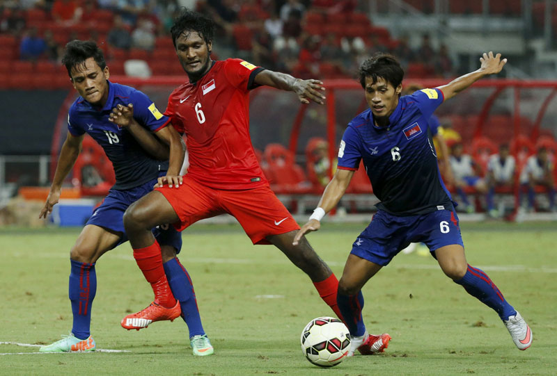Singapore's Madhu Mohana, center, is muscled off the ball by Cambodia's Nhim Sovannara, left, and Sam Oeun Pidor, right, during last night's World Cup qualifying match in Singapore. (Reuters)