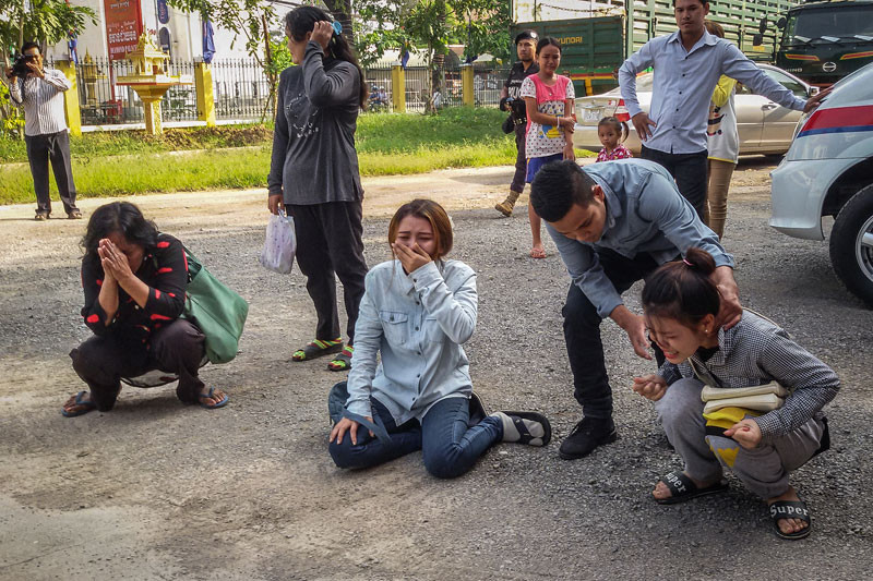 Yem Chrin's daughters, right and center, cry as their father is escorted into the Battambang Provincial Court yesterday. (Khy Sovuthy)