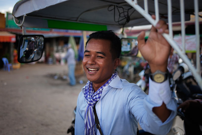 Phe Sophon stands next to his tuk-tuk at Choam Chao market in Phnom Penh on Wednesday. (Jens Welding Ollgaard/The Cambodia Daily)