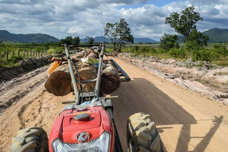 A tractor loaded with logs is parked on a dirt road in Oral district. (Peter Ford/The Cambodia Daily)
