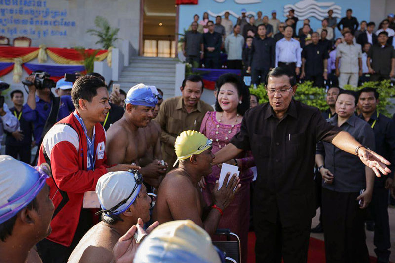 Prime Minister Hun Sen greets swimmers during the inauguration of the eponymously named Decho Sen Swimming Center in Kompong Cham province on Wednesday, in a photo posted to his official Facebook page.