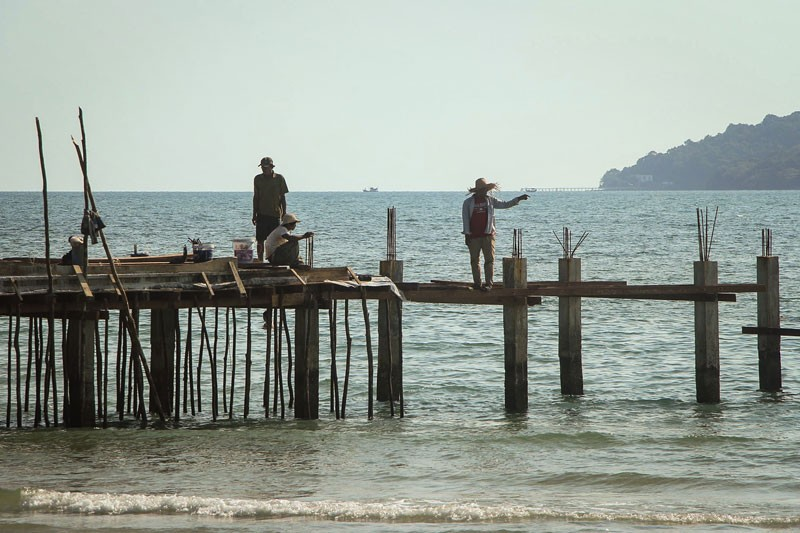 Men stand on the Royal Group's jetty on O'Tres Beach in Preah Sihanouk province on Thursday. (Seng Ou)