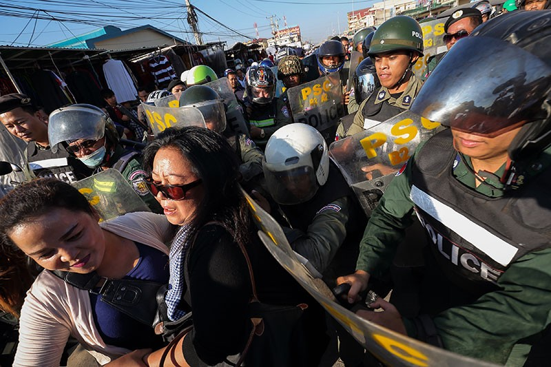 Riot police push Licadho director Naly Pilorge, in black, along Veng Sreng Boulevard in Phnom Penh on Sunday as she attempts to take part in a memorial ceremony (Satoshi Takahashi)