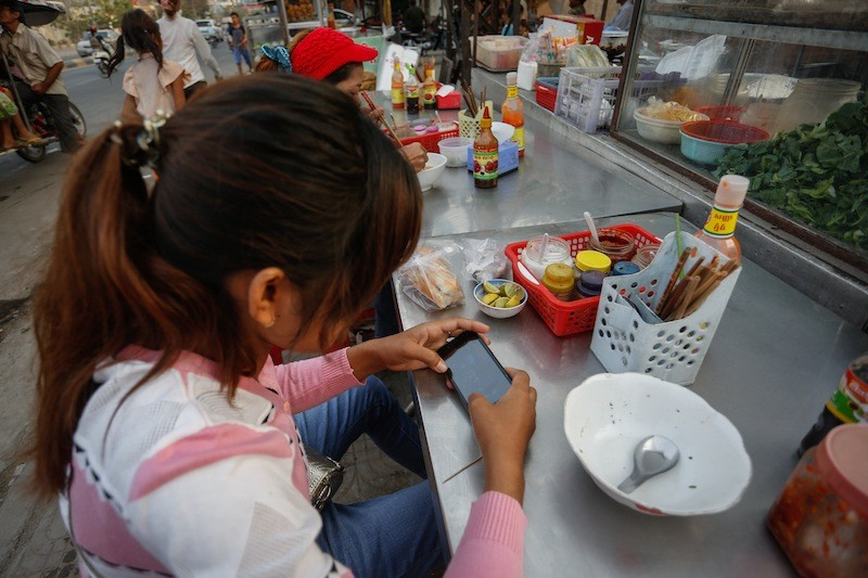 A woman uses a smartphone at a roadside restaurant in Phnom Penh on Tuesday. (Siv Channa/The Cambodia Daily)
