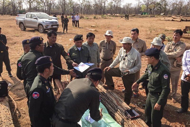 Police, military police and Forestry Administration officials inspect logs on the China Dynamic rubber plantation in Kratie province in January. (National Military Police)