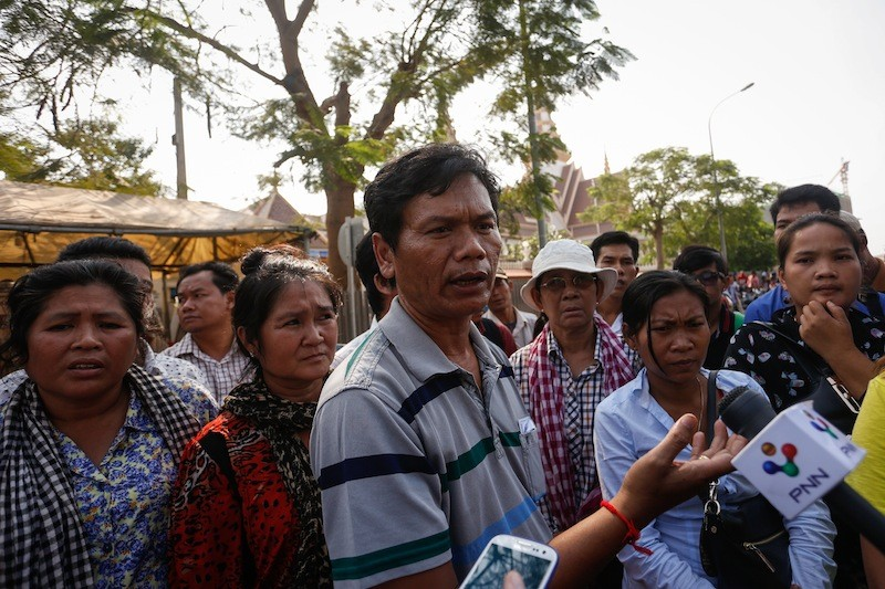 A representative of beachfront business owners from Preah Sihanouk province speaks to reporters outside the National Assembly in Phnom Penh on Thursday. (Siv Channa/The Cambodia Daily)