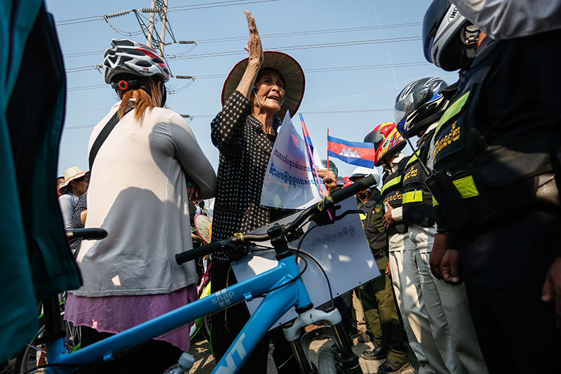 Participants in a planned International Women's Day bicycle ride are blocked by security guards while attempting to cycle to the National Assembly building in Phnom Penh on Tuesday. (Siv Channa/The Cambodia Daily)