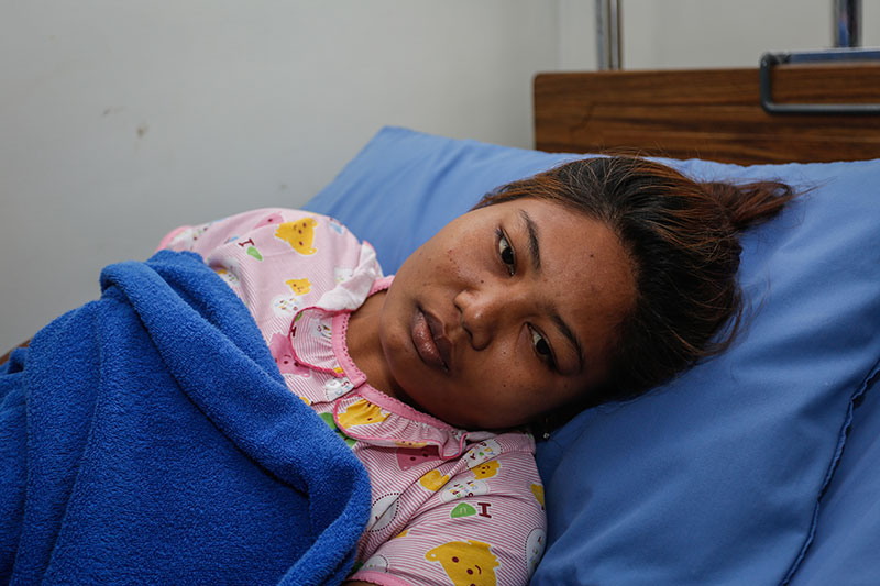 Phorn Sopheak lies in her hospital bed in Phnom Penh on Friday. (Siv Channa/The Cambodia Daily)