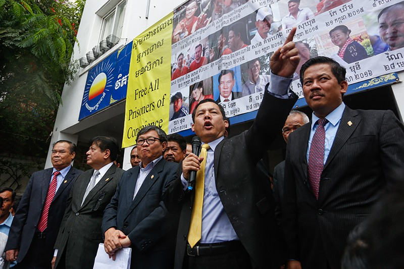 Flanked by fellow CNRP lawmakers, Eng Chhay Eang speaks to supporters outside the party's Phnom Penh headquarters yesterday. (Siv Channa/The Cambodia Daily)
