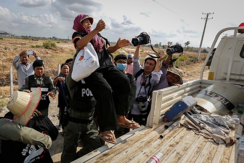 A land rights activist is pushed onto a truck by police in Phnom Penh's Dangkao district on Monday. (Reuters)