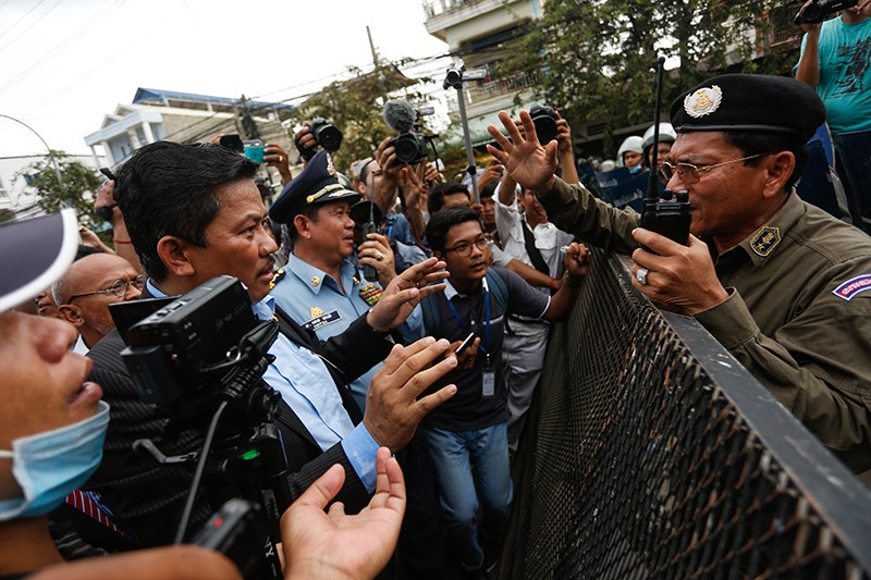 CNRP lawmaker and security chief Long Ry, left, negotiates the opening of National Road 2 with a police official near the opposition party's Phnom Penh headquarters yesterday. (Siv Channa/The Cambodia Daily)