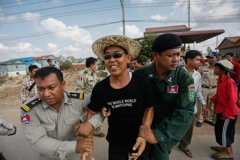 Police apprehend Thav Kimsan, deputy director of advocacy for rights group Licadho, on Monday morning in Phnom Penh's Dangkao district amid attempts to protest outside Prey Sar prison. (Siv Channa/The Cambodia Daily)