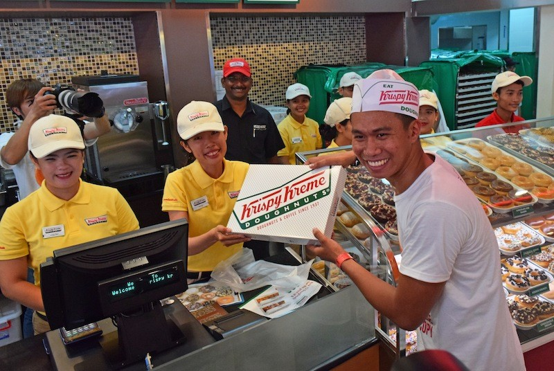 Yroll Desamparado, 24, collects his prize for being first in line at the opening of Phnom Penh's first Krispy Kreme store on Sunday morning. (Peter Ford/The Cambodia Daily)