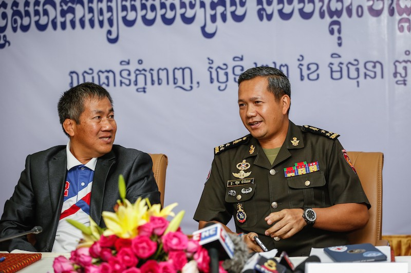 Vath Chamroeun, left, the National Olympic Committee's secretary-general, looks on as Hun Manet, the Cambodian Bokator Federation's deputy head, speaks at a news conference in Phnom Penh on Wednesday. (Siv Channa/The Cambodia Daily)