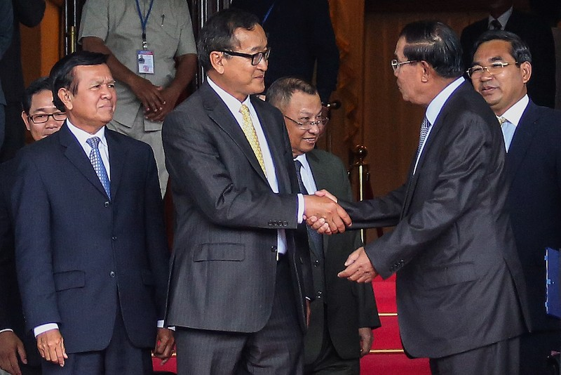 CNRP Vice President Kem Sokha grimaces as CNRP President Sam Rainsy shakes hands with Prime Minister Hun Sen after talks on July 22, 2014, that ended the opposition's post-election boycott of parliament. (Siv Channa/The Cambodia Daily)