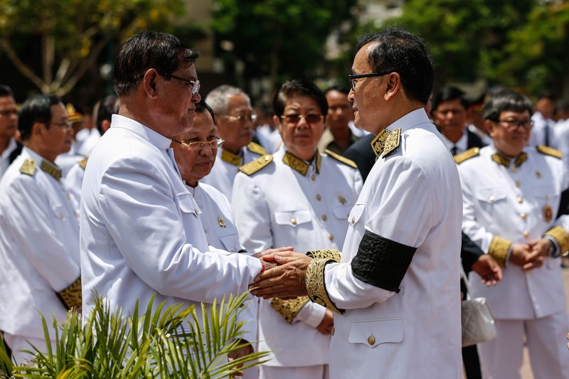 Interior Minister Sar Kheng and Senate President Say Chhum, both left, greet opposition leader Sam Rainsy at the funeral for late CPP President Chea Sim in June 2015. (Siv Channa/The Cambodia Daily)