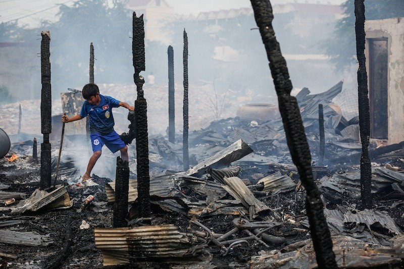 A boy rummages through the charred remains of 33 houses in Phnom Penh's Meanchey district after a fire swept through the area yesterday afternoon. (Siv Channa/The Cambodia Daily)