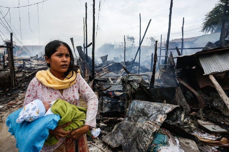 A woman holds an infant amid the charred remains of 33 houses in Phnom Penh's Meanchey district after a fire swept through the area yesterday afternoon. (Siv Channa/The Cambodia Daily)