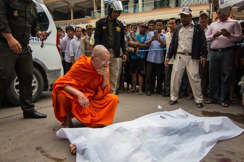 The father of slain Defense Ministry official Ly Davy weeps after identifying his daughter's body at the scene of her murder in Phnom Penh's Tuol Kok district on Tuesday morning. (Peter Ford/The Cambodia Daily)
