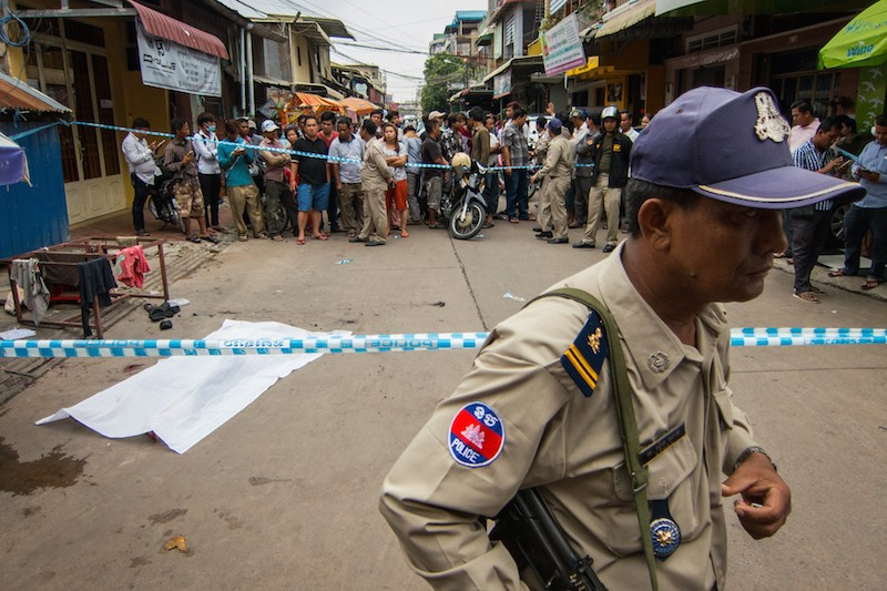 A police officer guards the cordoned-off area where Defense Ministry official Ly Davy was killed in Phnom Penh's Tuol Kok district yesterday morning. (Peter Ford/ Cambodia Daily)