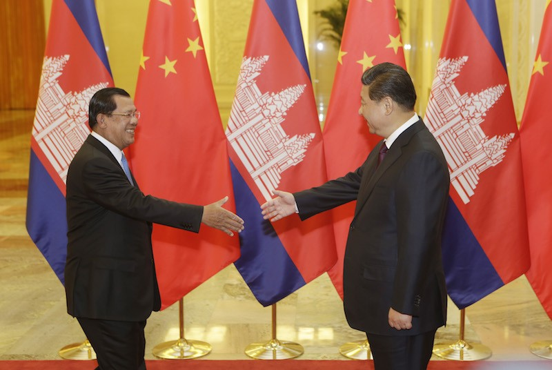 Prime Minister Hun Sen, left, shakes hands with Chinese President Xi Jinping before a meeting in Beijing in November 2014. (Reuters)
