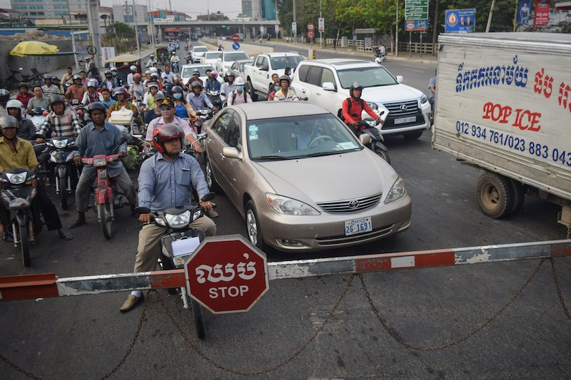 Motorists stop at a railway crossing in Phnom Penh's Tuol Kok district as a passenger train passes in April. (Peter Ford/The Cambodia Daily)