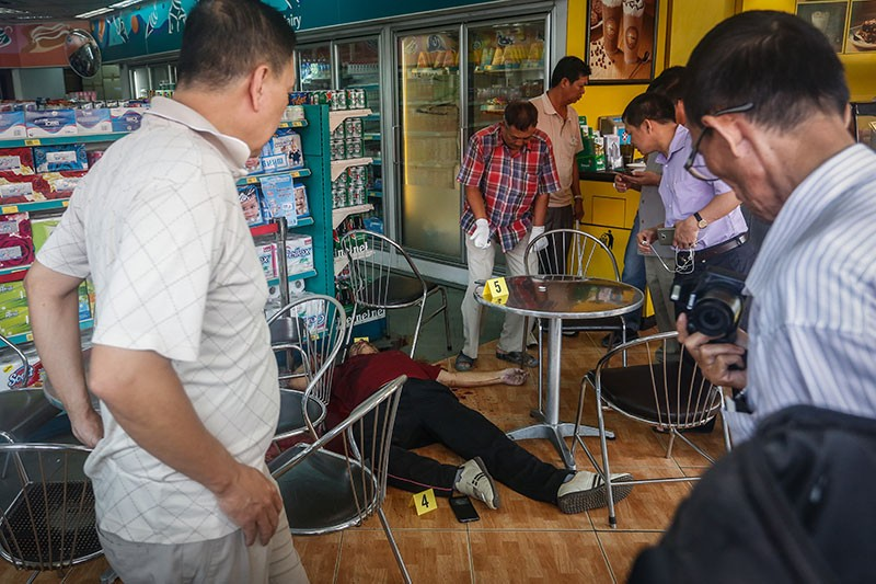 Police officers inspect the scene of prominent political analyst Kem Ley's murder at a gas station in Phnom Penh on Sunday morning. (Siv Channa/The Cambodia Daily)