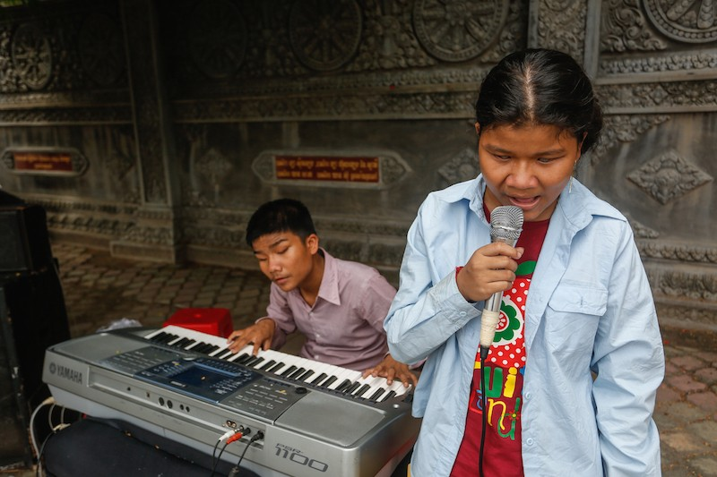 Chhoeuy Tola and Chhoey Srey Pov perform on Sihanouk Boulevard in Phnom Penh yesterday. (Siv Channa/The Cambodia Daily)