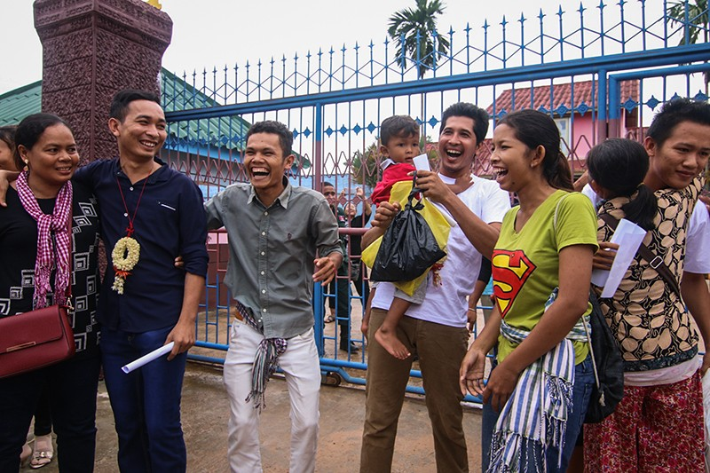Environmental activists San Mala, left, Sim Samnang, center in white, and Try Sovikea, far right, greet friends and relatives upon leaving the Koh Kong Provincial Prison on Friday afternoon. (Central)