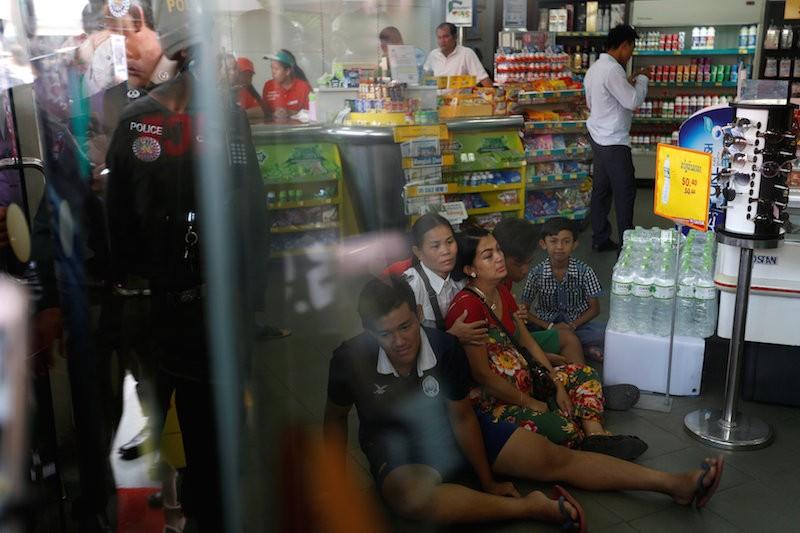 Kem Ley's wife, Pou Rachana, is comforted inside the gas station where her husband was killed on Sunday. (Pring Samrang/Reuters)