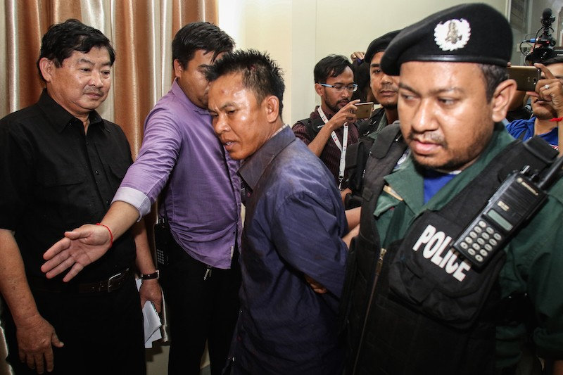 The alleged killer, Chuob Samlab, is brought into the Phnom Penh municipal police headquarters during a press conference on Sunday. (Khem Sovannara)