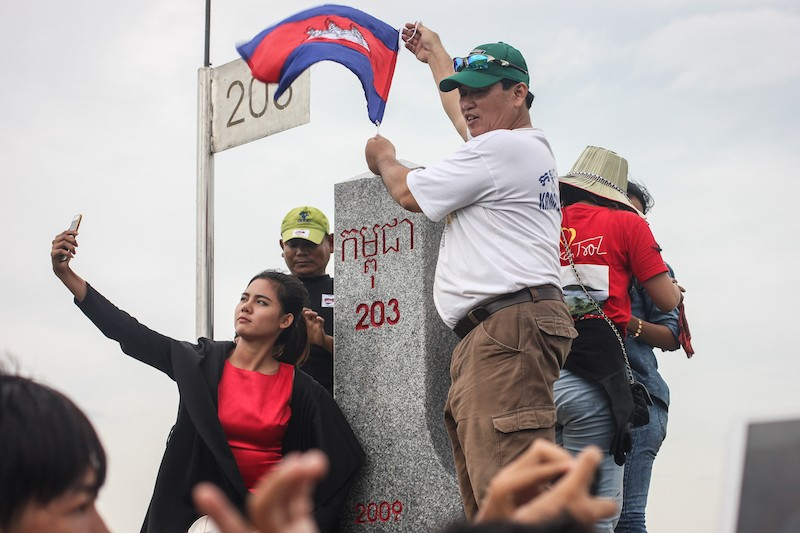 Thy Sovantha shoots a video of herself at a marker on the Vietnam border during a CNRP-led trip to Svay Rieng province in July last year. (Alex Willemyns/The Cambodia Daily)