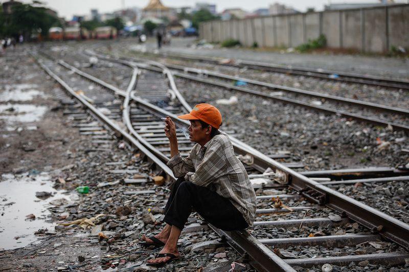 A man smokes near homes built next to railway tracks in Phnom Penh on Wednesday. (Siv Channa/The Cambodia Daily)