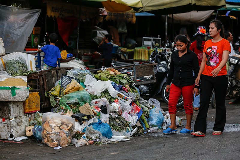 Young women walk past a pile of garbage outside Phsar Kap Kor market in Phnom Penh on Thursday. (Siv Channa/The Cambodia Daily)
