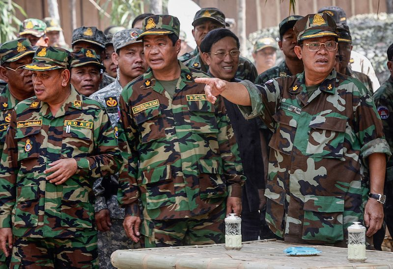 From left: Deputy military commanders Chea Dara and Kun Kim stand next to Prime Minister Hun Sen during a meeting with soldiers near the Thai border in Preah Vihear province in 2010. (Reuters)