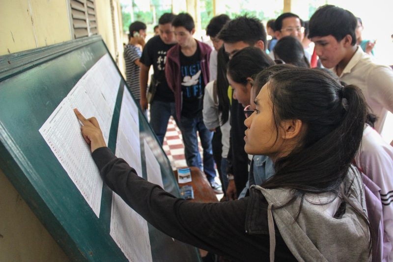 Students search for their exam scores on a list posted at Preah Yukunthor High School in Phnom Penh on Saturday afternoon. (Janelle Retka/The Cambodia Daily)