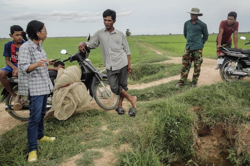 Leang Chanthy, left, speaks with farmers alongside rice fields in Takeo province last month, in a photograph provided by the Rat Hunter team.