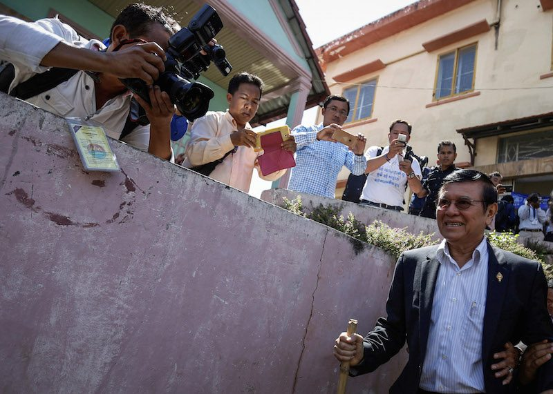 Deputy opposition leader Kem Sokha walks past reporters on Wednesday on his way to register to vote in Phnom Penh's Meanchey district. (Reuters)