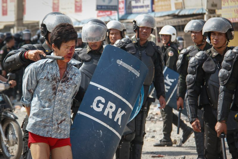 Military police escort a bloodied protester away from Veng Sreng Street in Phnom Penh after suppressing protests in January 2014. (Neou Vannarin/The Cambodia Daily)