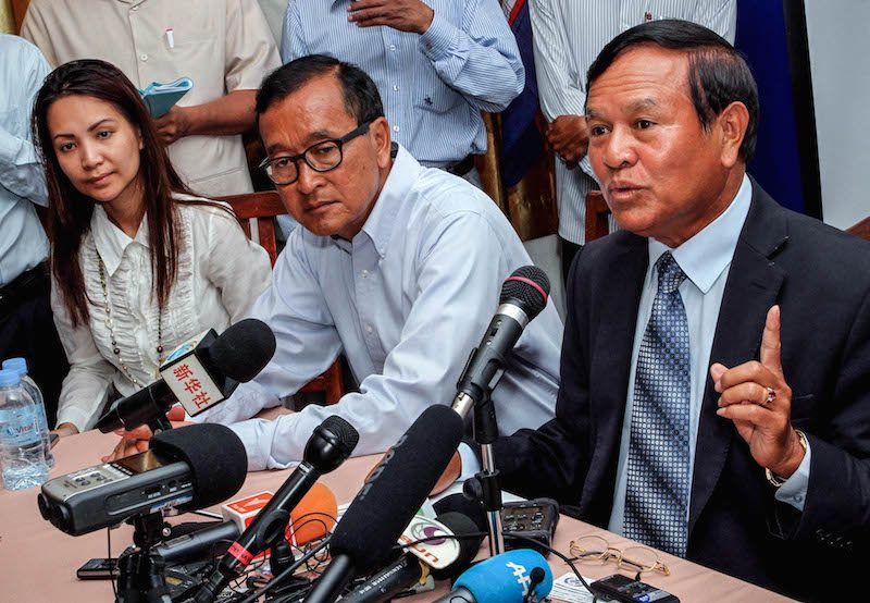 Deputy opposition leader Kem Sokha, right, speaks at a news conference on the day before the national election in July 2013. Kem Monovithya is seated to the left of opposition leader Sam Rainsy, center. (Siv Channa/The Cambodia Daily)