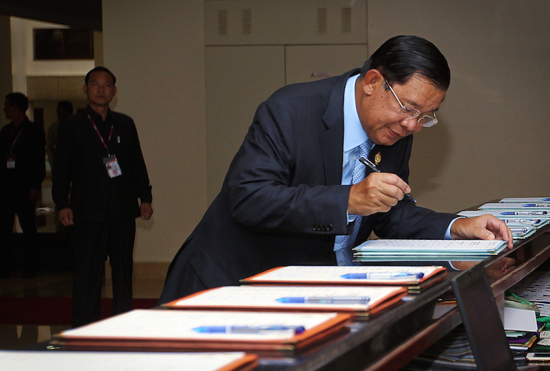 Prime Minister Hun Sen signs into the National Assembly prior to parliament's passage of the national budget on Wednesday. (Pring Samrang/Reuters)