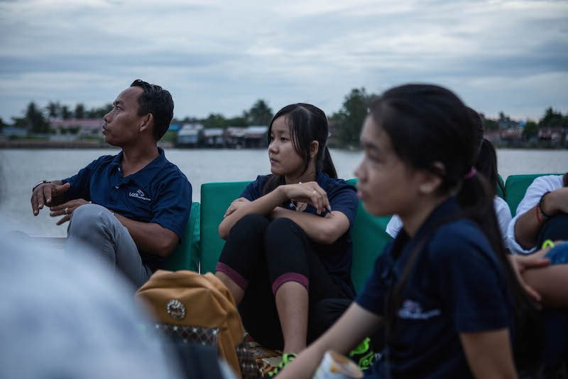 A Liger Learning Center staff member, left, and student attend a boatside book reading at the Kampot Writers and Readers Festival on Friday evening. (Hannah Hawkins/The Cambodia Daily)