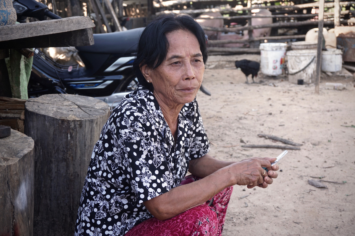 Heng Lao, 60, a holdout at the Kbal Chhay site, squats in front of her coops of chickens and pigs. (Aisha Down/The Cambodia Daily)